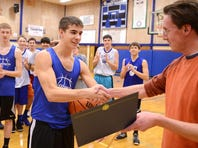 Sports reporter Bill Poehler presents Amity's Zach Wilson with the Statesman Journal Athlete of the Week award during practice on Monday.