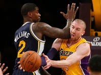 Los Angeles Lakers' Steve Blake, right, takes an elbow in the face from Utah Jazz's Marvin Williams, right, as he passes the ball of to Jordan Hill, not pictured, to score during the first half of an NBA basketball game in Los Angeles, Tuesday, Feb. 11, 2014. (AP Photo/Danny Moloshok)