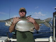 This angler, guided by Steven Davis, hefts a lake trout estimated at 40 lbs. It was returned.