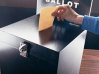 Man Inserting a Voting Form into a Ballot Box