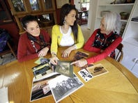 Mia Prickett, middle, shares a collection of family photos with great aunt's Marilyn Portwood, right, and Val Alexander in Portland, Ore., Thursday, Jan. 16, 2014.