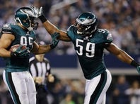 After intercepting the ball from Dallas Cowboys quarterback Kyle Orton, Philadelphia Eagles inside linebacker Mychal Kendricks (95) celebrates with inside linebacker DeMeco Ryans (59) during the first half of a game on Sunday.