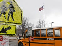 A JCPS school bus leaves outside Cochran Elementary School in January 2012 after an early dismissal due to pending snow and cold weather. (By Matt Stone, The Courier-Journal) Jan.12, 2012