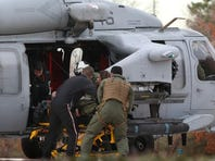 The pilot of an F/A-18 Super Hornet, from Strike Fighter Squadron 143, is taken from a Navy helicopter to Norfolk Sentara General Hospital, Wednesday in Norfolk, Va.