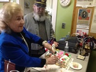 Eva Newman, supervisor of the First White House of the Confederacy, slices cake Monday at the celebration of the birthday of Robert E. Lee. At right is Henry Howard, a Civil War re-enactor wearing a  Confederate Army uniform.