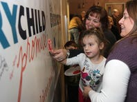 Evangeline Cashmore adds her handprint to a banner that community members signed as a pledge to put children and families first on Tuesday. The Every Child Promise announced its 10-year strategic plan to significantly improve the lives, and futures, of Springfield's children.