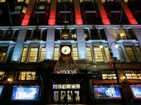 Macy's department store in Herald Square is illuminated with holiday lighting on Dec. 17, 2013, in New York. Macy's said Wednesday it is laying off 2,500 workers as it restructures business.