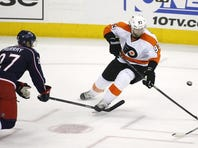 Philadelphia Flyers' Jakub Voracek (93), of the Czech Republic, tries to control the puck as Columbus Blue Jackets' Ryan Murray (27) closes in during the third period of an NHL hockey game on Saturday, Dec. 21, 2013, in Columbus, Ohio. (AP Photo/Mike Munden)