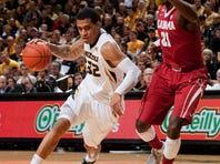 Missouri's Jabari Brown dribbles around Alabama's Rodney Cooper during the first half Saturday in Columbia, Mo. Brown scored 24 points in the Tigers' 68-47 victory.
