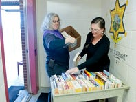 From left, Jill Ellern, systems librarian at WCU's Hunter Library, and Liz Gregg, assistant county librarian at Jackson County Public Library, part of the Fontana Regional Library system, deliver and sort books for the library at the Macon County Detention Center.