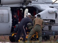 The pilot of an F/A-18 Super Hornet, from Strike Fighter Squadron 143, is taken from a Navy helicopter to Norfolk Sentara General Hospital on Wednesday in Norfolk, Va. The jet crashed about 50 miles off the coast of Virginia Beach, Va.