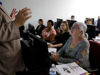 Rosi Pozzi, 73, of Davie, Fla., right, listens during a job search workshop at WorkForce One, in Davie, Fla.