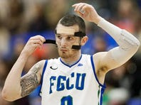 .FGCU point guard Brett Comer puts on a protective mask during play against ETSU on Saturday at Alico Arena. Comer broke his nose in the final seconds of play against USC Upstate on Thursday. He borrowed the mask from teammate Nate Hicks.  KINFAY MOROTI/THE NEWS-PRESS
