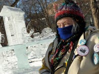 Joan Kelly of St. Paul, Minn.,was decked out in Winter Carnival Buttons and warm clothes as she visited the ice sculptures in St. Paul's Rice Park as another polar blast brought sub-zero temperatures in the teens with wind chills as high as the minus-40's to much of Minnesota on Monday.
