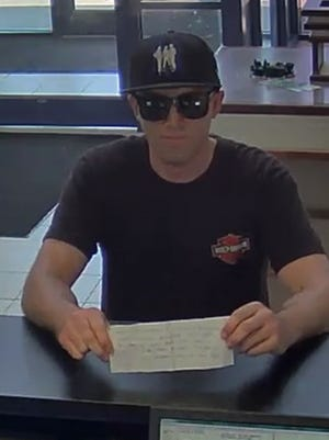 State police released this image of the suspect in Sunday's TD Bank robbery in Fishkill, holding the note police say he handed to the teller.