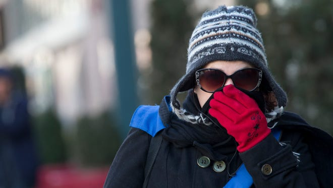 A woman lifts her scarf up in front of her nose to shield from the cold air,  Feb. 12, 2016, in New York City.
