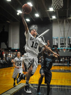Onate High School's Antonio Zamora, center, beats Cleveland's Jayden Phillips to the basket during high school basketball action on Tuesday at OHS. Cleveland won 65-59 in overtime. The OHS girls beat Cleveland 57-38 in the first game of Tuesday's doubleheader.