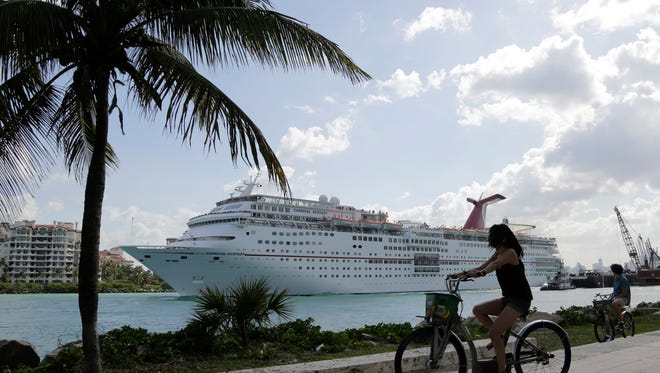 In this Monday, May 19, 2014 photo, the Carnival Cruise Lines ship Ecstasy leaves the Port of Miami as it passes Miami Beach, Fla.