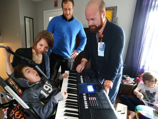 Elias Wendland gets help with music therapy from Brian Schreck (right) and parents Emma and Stephen Wendland. Diagnosed with Krabbe disease, Elias cannot speak, see or move well, but he can hear and he seems to have a powerful connection to music. On the right is Elias' brother Leo.