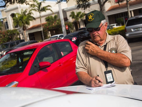 Collier County Sheriff's Office volunteer William Leach runs a license plate of a car with visible valuables inside in the parking lot of Shoppes at Vanderbilt on Wednesday, Jan. 4, 2017. The burglary prevention initiative was conducted by the Collier County Sheriff's Office.