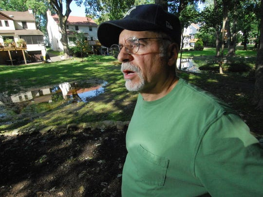 Greenwood Drive resident David Emma surveys his and his neighbors' flood ravaged backyards in September 2011 after their South Mountain neighborhood in Millburn was inundated with floodwaters from the Rahway River during Tropical Storm Irene.