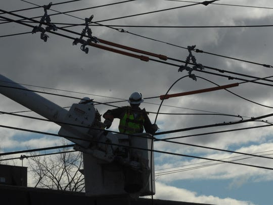 PSE&G line men repair wires felled by Sandy on Moonachie
