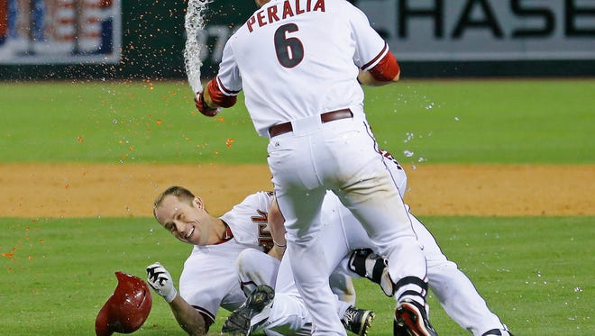 Arizona Diamondbacks second baseman Aaron Hill (2) is doused by teammate David Peralta (6) after Hill's walk-off single in the 14th inning of their MLB game against the Cleveland Indians Tuesday, June 24, 2014 in Phoenix, Ariz.