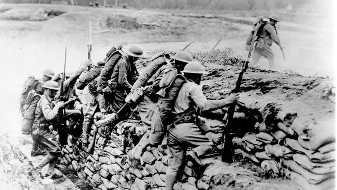 American troops climb over a sandbag revetment in France during World War I in  1918.