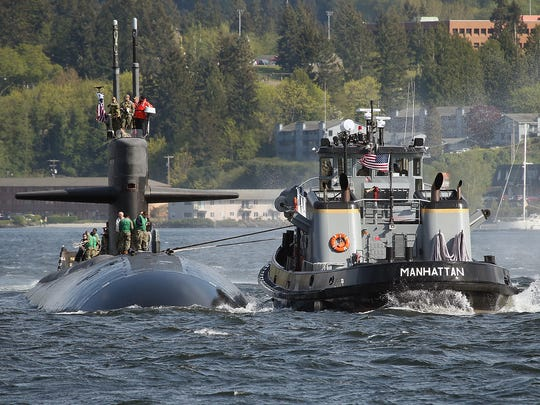 A Navy tug helps guide the USS Bremerton to the pier as it arrives at Naval Base Kitsap-Bremerton on April 27, 2018.