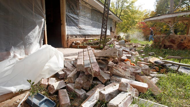 In this Nov. 6, 2011 file photo, Chad Devereaux works to clear up bricks that fell from three sides of his in-laws' home in Oklahoma after two earthquakes hit the area in less than 24 hours. A government report released Thursday, April 23, 2015 found that a dozen areas in the United States have been shaken in recent years by small earthquakes triggered by oil and gas drilling.  The man-made quakes jolted once stable regions in eight states, including parts of Alabama, Arkansas, Colorado, Kansas, New Mexico, Ohio, Oklahoma and Texas, according to researchers at the U.S. Geological Survey.