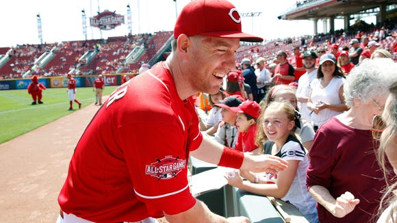 The Reds' Todd Frazier smiles after taking photos with fans before the Reds' game against Milwaukee on April 29.