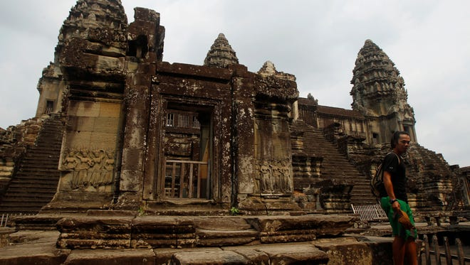 A tourist stands at Angkor Wat in Siem Reap, Cambodia, on March 21, 2015.