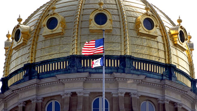 An American flag flies near the dome of the Iowa Capitol building in 2013.