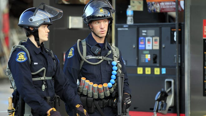 Jeff Roberson/AP Police wearing riot gear stand outside a convenience store that had been burned and looted Aug. 11, 2014, after the Aug. 9 shooting death of Michael Brown in Ferguson. FILE - In this Aug. 11, 2014, file photo, police wearing riot gear stand outside a convenience store that had previously been burned and looted a day after the shooting of Michael Brown in Ferguson, Mo. The shooting of Brown has prompted a flurry of legislation in his home state, where politicians are proposing to curb police tactics, prosecutorial powers and even traffic fines in an attempt to address concerns that have fueled nationwide protests. (AP Photo/Jeff Roberson, File)