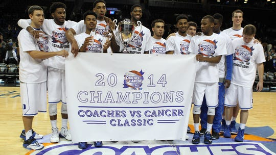 The Duke Blue Devils celebrate with the trophy after