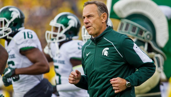 Michigan State head coach Mark Dantonio, run on to the Michigan Stadium field with his team before the an NCAA college football game against Michigan in Ann Arbor on Oct. 17, 2015.