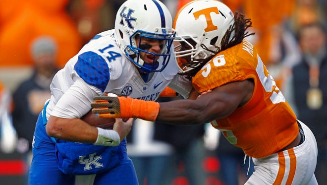 Kentucky quarterback Patrick Towles (14) is hit by Tennessee linebacker Curt Maggitt (56) during last year's game in Knoxville.