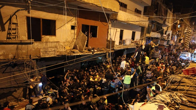 Emergency personnel and civilians gather at the site of a twin suicide bombing in Burj al-Barajneh, in the southern suburbs of the capital Beirut on Nov. 12, 2015.