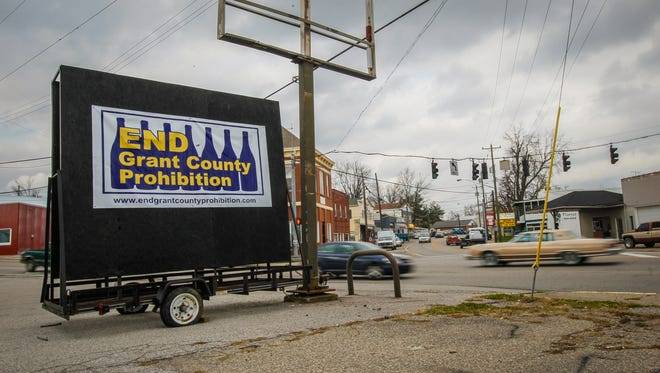 """Car drive past a sign that reads """"END Grant County Prohibition"""" along the main road through Dry Ridge. Grant County voters will head to the polls in order to decide whether or not to make Grant County a """"wet"""" county on a Dec. 22 ballot."""