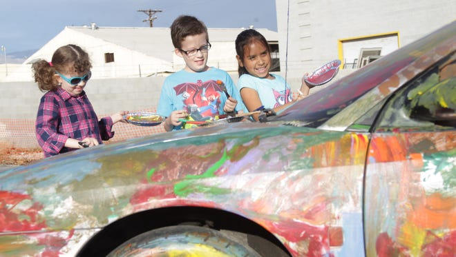 From left to right, Isabella Diaz, Ricardo Diaz and Julissa Serna paint a car at the Coachella Valley Historical Museum in Indio during their first held car show on January 22, 2016.