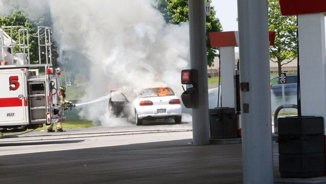 No one was injured when this car caught on fire and the driver pulled off into a gas station.