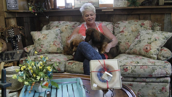 Mary Hall in her shop with her two dogs, Stella and Skylar. Stella and her mother Skylar are regular fixtures at Crows Nest.