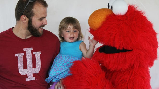 Ryan McVey and Josi McVey from Fairland Indiana get their photo taken with Elmo. Saturday June 9th, 2012, PBS fans of all ages gathered in the park for the PBS KIDS in the Park event.  (Michelle Pemberton/The Indianapolis Star)