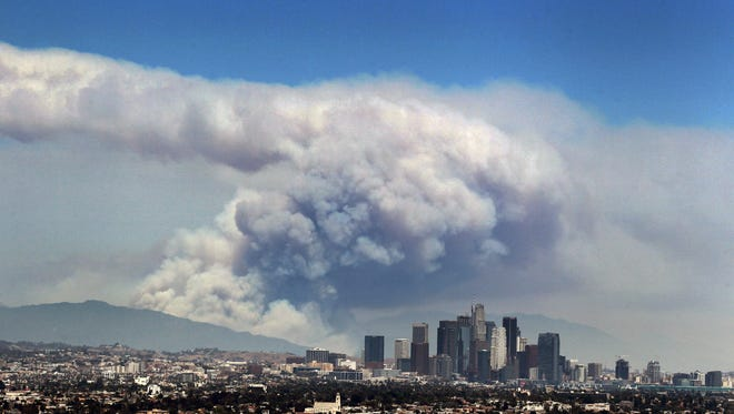 Smoke from wildfires burning in Angeles National Forest fills the sky behind the Los Angeles skyline on Monday, June 20, 2016. The wildfires several miles apart devoured hundreds of acres of brush on steep slopes above foothill suburbs erupted in Southern California as an intensifying heat wave stretching from the West Coast to New Mexico blistered the region with triple-digit temperatures.