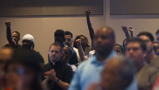 Community members raise their fists in a show of solidarity during a press conference and rally at First Institutional Baptist Church in Phoenix on Thursday, July 7, 2016. Two black men, Alton Sterling and Philando Castile, were killed by police in separate incidents Tuesday and Wednesday, sparking protests across the country.