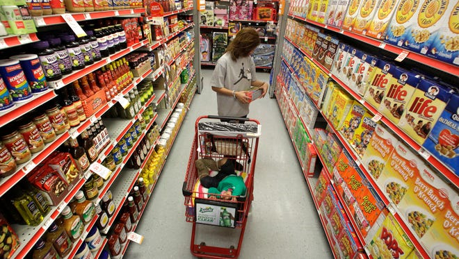 FILE - In this Dec. 14, 2010, file photo, Alicia Ortiz shops through the cereal aisle as her daughter Aaliyah Garcia catches a short nap in the shopping cart at a Family Dollar store in Waco, Texas. Up and down supermarket aisles, rows of perfectly placed products reflect calculated deliberations aimed at getting shoppers to spend more.  Take cereal, for example. Research published in the Journal of Environment and Behavior found that kids' cereals tended to be placed on lower shelves where they are more eye-level with children. It's just one example of the tactics food companies and supermarkets use to sway what people put in their carts. (AP Photo/Tony Gutierrez, File)