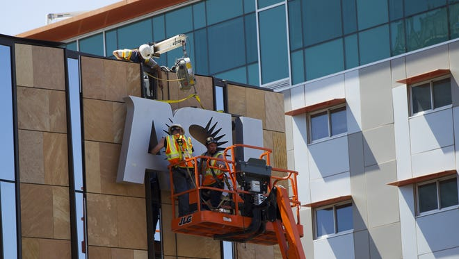Construction workers hang an Arizona State University sign at the Arizona Center for Law and Society in downtown Phoenix on July 26, 2016. The building will be home to ASU's Sandra Day O'Connor College of Law.