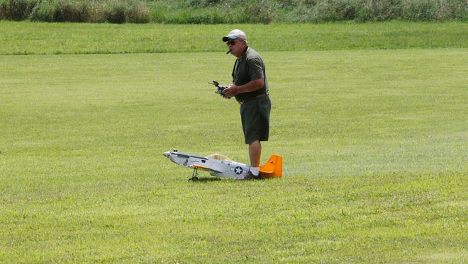 Jerry Dillman of Delphi taxis his remote-controlled P-51D to the runway for takeoff Saturday during an open house at the model aircraft club's landing strip in Lafayette.