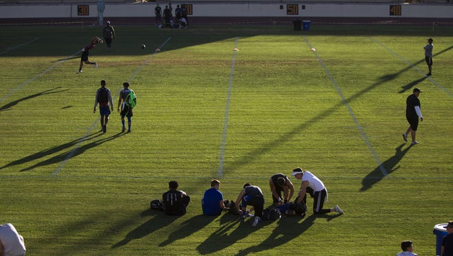 High school football players warm up before a satellite camp on Wednesday, June 15, 2016, at Hoy Stadium at Phoenix College.