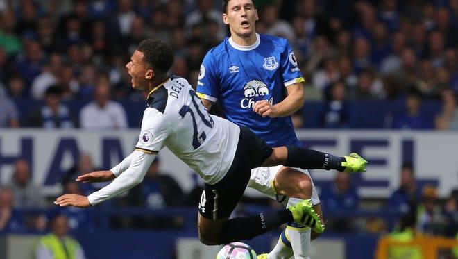 Tottenham Hotspur's English midfielder Dele Alli (L) goes down in a challenge with Everton's English midfielder Gareth Barry.